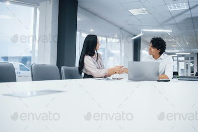 Successful deal between two people that sitting near table and laptop on it in the white office