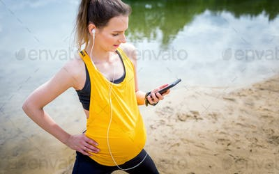Pregnant woman using fitness app during exercises outdoor