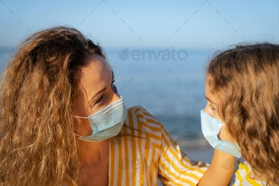 Happy mother and daughter wearing medical mask outdoor