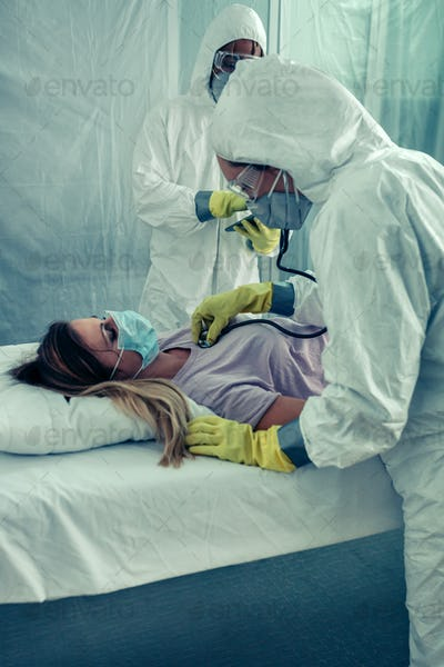 Doctors with bacteriological protection suits attending a patient