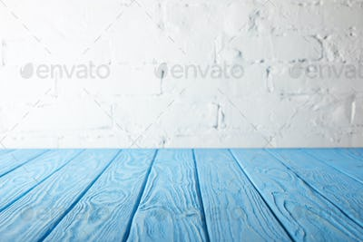 light blue wooden tabletop and white wall with bricks