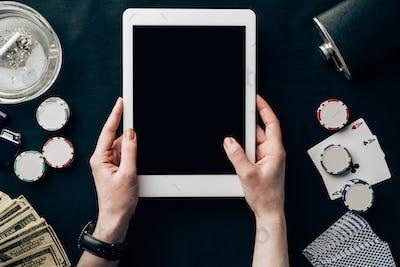 Female hands holding digital tablet on casino table