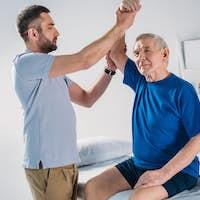portrait of rehabilitation therapist doing massage to senior man on massage table
