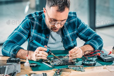 Hardware engineer in glasses soldering pc parts