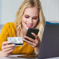 beautiful smiling young woman holding credit card and using digital devices