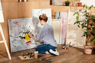 back view of attractive girl painting in art studio