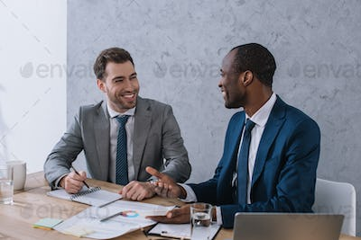 Smiling businessmen working at table with papers in office