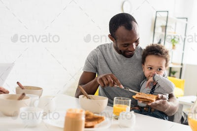father applying peanut butter on toast for little son