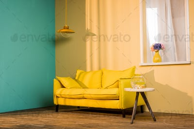 yellow sofa and aquarium on table in living room
