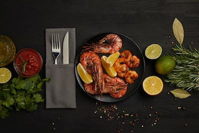 flat lay with grilled shrimps with lemon pieces on plate and arranged sauce, spices, ingredients and