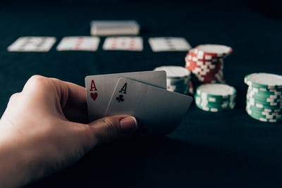 Woman holding playing cards by casino table