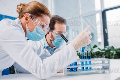 researchers in white coats and medical masks working with reagents together in lab