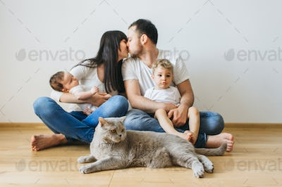 parents kissing each other with two sons and grey british shorthair cat on hands at home