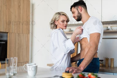 seductive young woman taking off t-shirt from handsome boyfriend in kitchen