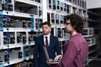 successful businessman and computer engineer working together at bitcoin mining farm
