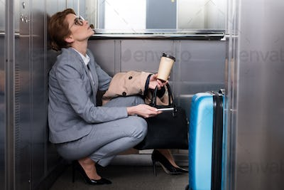 side view of tired businesswoman in suit with smartphone and coffee to go in elevator