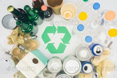 top view of different types of trash with recycle sign on white