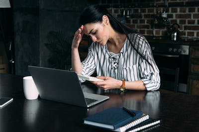 depressed young woman with calculator and laptop counting tax at home on kitchen