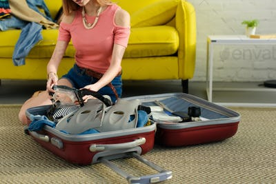 cropped view of girl packing goggles and snorkeling fins into suitcase for travel