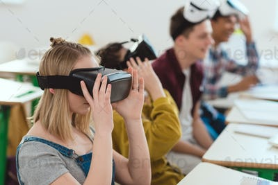 Side view of high school students taking off virtual reality headsets