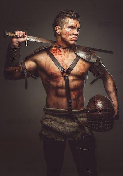Muscular shirtless gladiator holding helmet and sword.
