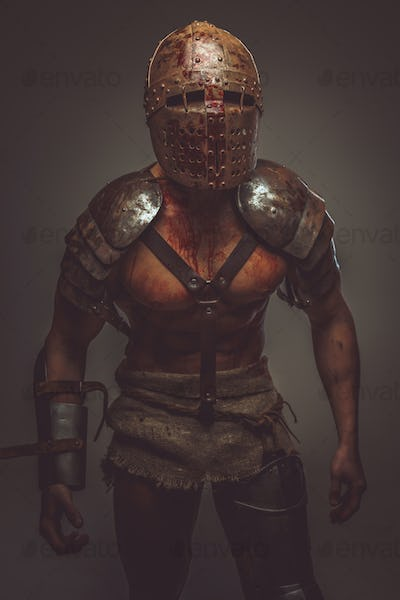 Bloody gladiator in armor and helmet.