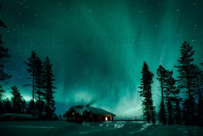 Northern lights Aurora Borealis activity over wooden cottage in winter Finland