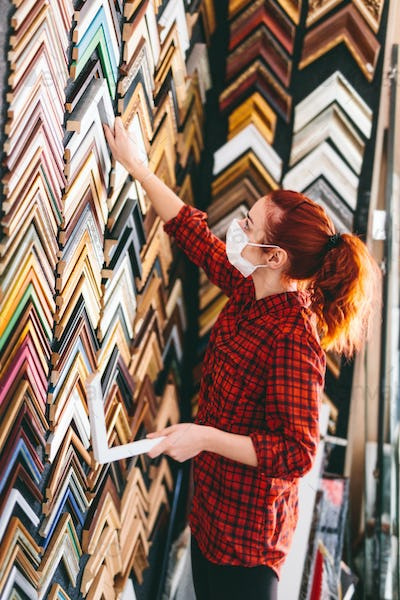 Woman shop assistant in face mask working in picture frames store
