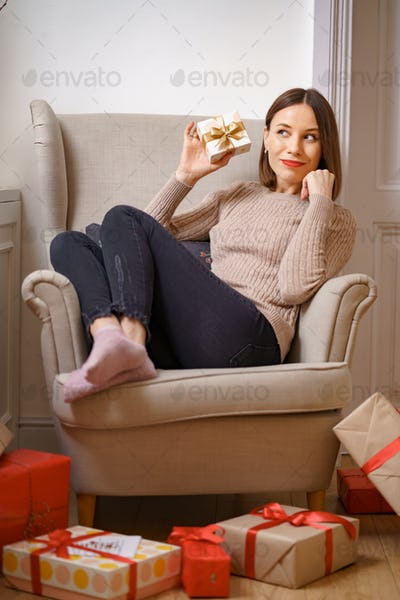 Woman sitting in an armchair at home with a present in her hand