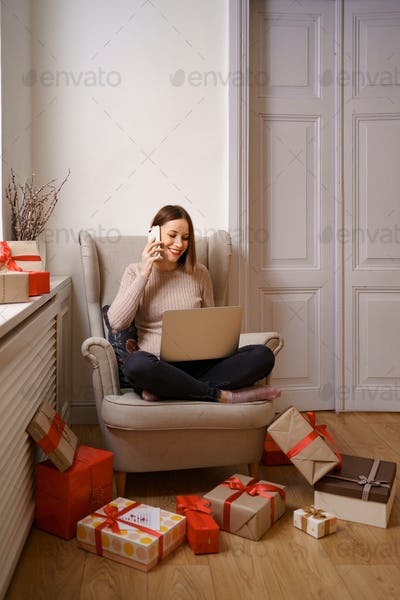 Woman sitting in an armchair at home, working on laptop computer, talking on mobile phone