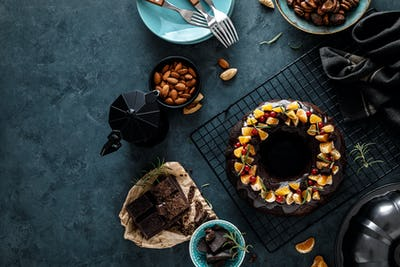 Christmas chocolate bundt cake with ganache decorated with oranges, berries and rosemary