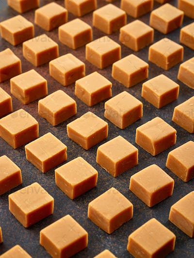 pattern of caramel candies on dark background, selective focus