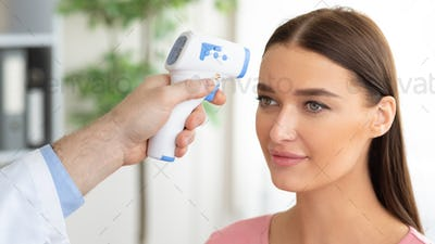 Doctor checking temperature of female patient using infrared thermometer