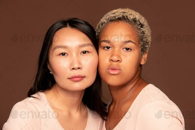 Two young intercultural females looking at camera while touching by faces