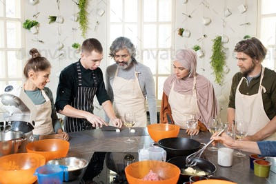 Young male cooking expert or coach chopping onions on board among four trainees