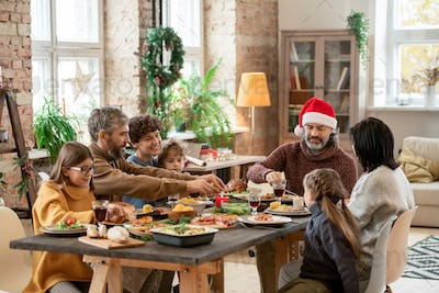 Happy multi-generation family sitting by served festive table on Christmas day