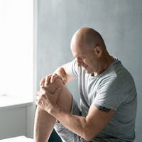 Contemporary bald mature sportsman in grey t-shirt and shorts massaging knee