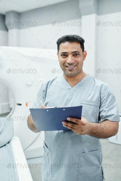 Successful mixed-race male doctor in uniform making notes in medical document