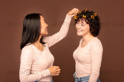 one of two young intercultural women putting small flower in hair of her friend