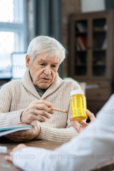 Senior man looking and pointing at bottle of pills in hands of female doctor