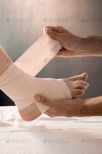 Hands of clinician holding foot of male patient while wrapping it with bandage