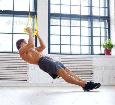 Sporty male exercising with fitness trx straps.