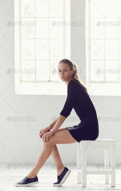 Slim young woman in shirt black dress.