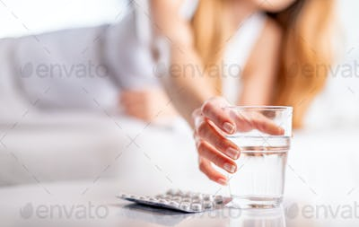 Suffering sick woman in bed taking pills and glass of water