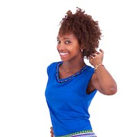 Young African American woman making braids to her frizzy afro hair - Black people