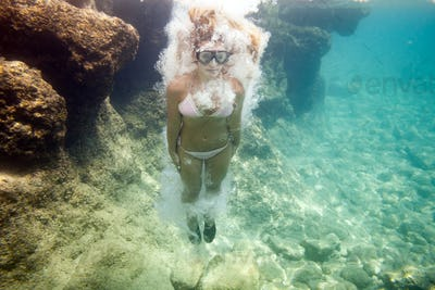 Young woman jumping to water, underwater image