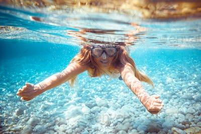 Girl snorkeling underwater in the tropical sea