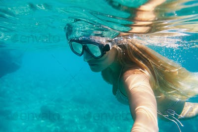 Young woman snorkeling underwater in the tropical sea