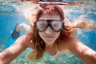 Beautiful woman underwater snorkeling in the clear tropical water