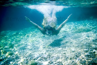 Snorkeling in the tropical sea, woman with mask diving underwater